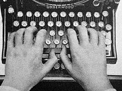 Photo of hands typing on an old typewriter.